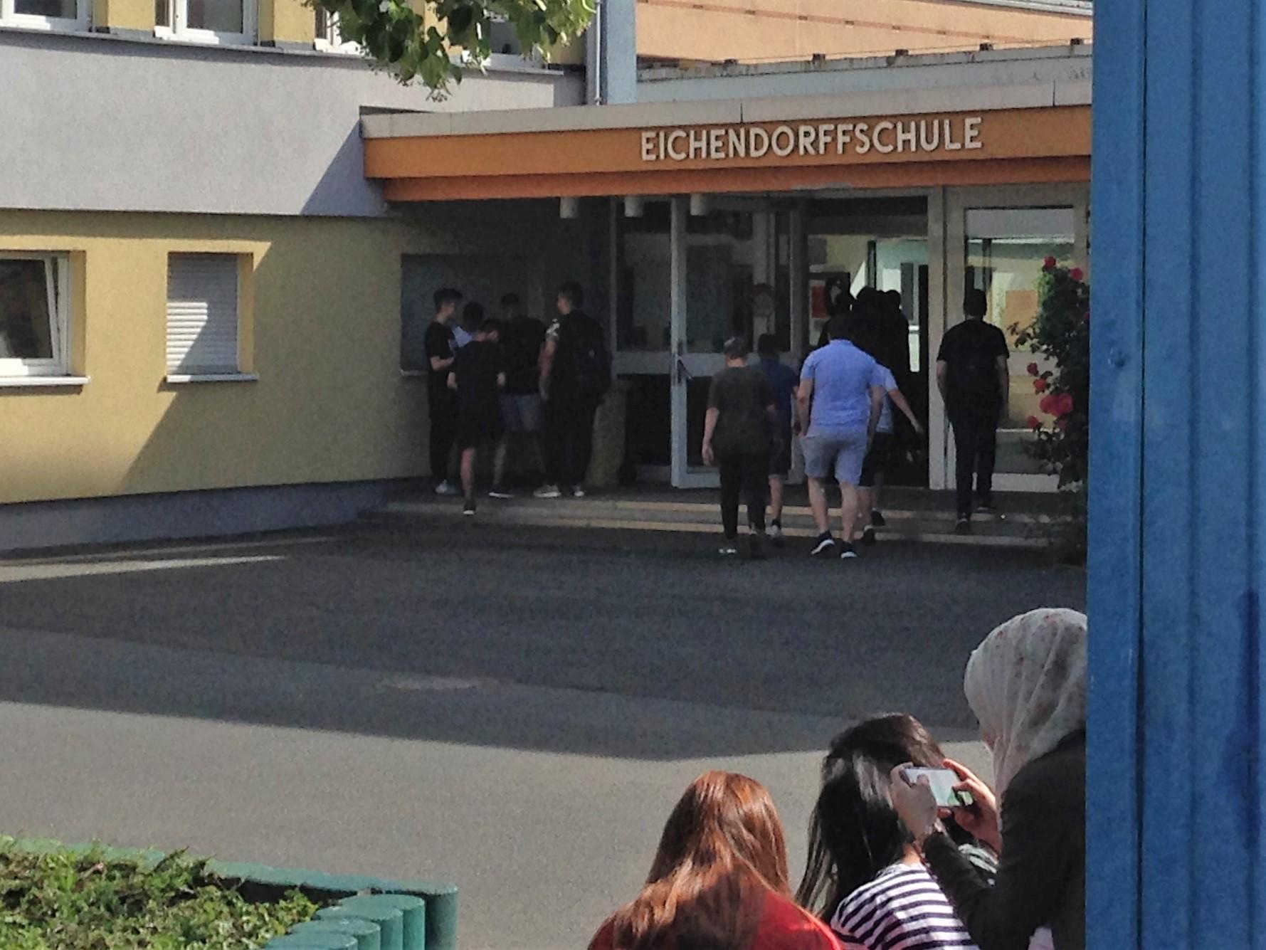 Das Bild zeigt den Eingan der Eichendorff-Mittelschule Erlangen mit mehreren Schülerinnen und Schülern davor.